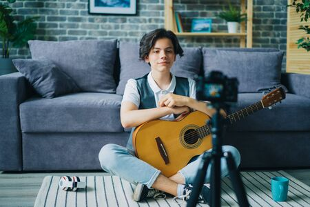 Creative teenager recording video about playing guitar holding instrument talking smiling using professional camera on tripod. People and vlogging concept.