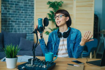 Female blogger recording audio in sound studio talking in microphone with serious face sitting at desk alone. Blogging, business and modern devices concept.