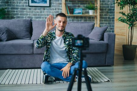 Handsome young man blogger is recording video for internet vlog talking smiling waving hand using camera on tripod sitting on floor in studio apartment. People and lifestyle concept.