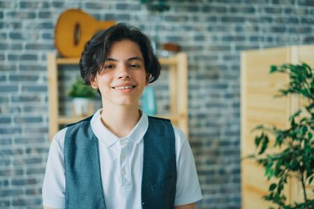 Portrait of attractive teenage boy smiling looking at camera standing alone at home feeling happy and relaxed. Carefree childhood and people concept.