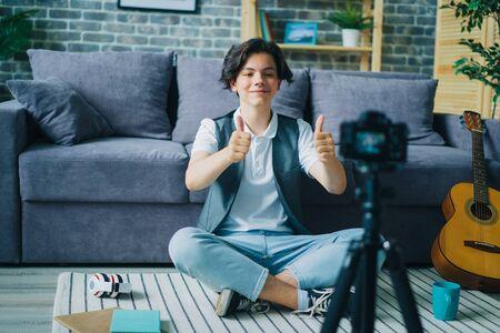 Creative boy showing thumbs-up sitting on floor in front of camera recording video for internet vlog. Modern lifestyle, happiness and people concept.