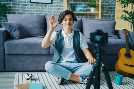 Joyful teenage boy speaking smiling gesturing in front of camera at home recording video for internet vlog. Modern technology and youth lifestyle concept. 免版税图像
