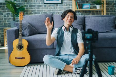 Happy teenage boy vlogger is waving hand and smiling sitting in front of camera at home recording video for internet vlog. Youth and modern lifestyle concept. Zdjęcie Seryjne