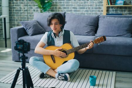 Teenage guitarist recording video for internet blog holding guitar sitting on floor at home looking at camera on tripod. Music, teenagers and hobby concept.