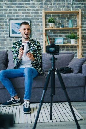 Male blogger is recording video about modern headphones talking looking at camera holding gadget. Electronic devices, young people and blogging concept. Zdjęcie Seryjne