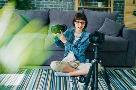 Creative blogger young woman recording video about virtual reality glasses sitting on floor at home holding modern ar device. People and equipment concept.