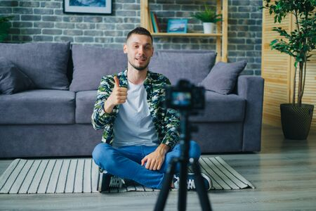 Happy young man vlogger recording video for online internet vlog using camera showing thumbs-up smiling gesturing. Blogging and modern people concept. 免版税图像