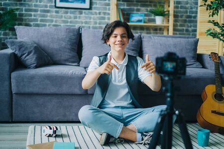 Handsome teenager is showing thumbs-up recording video for internet vlog at home creating content for online blog. People, blogging and lifestyle concept. 免版税图像