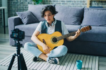 Cheerful handsome teenage blogger boy talking for camera holding guitar sitting on floor at home. Creative youth, modern apartment and blogging concept.
