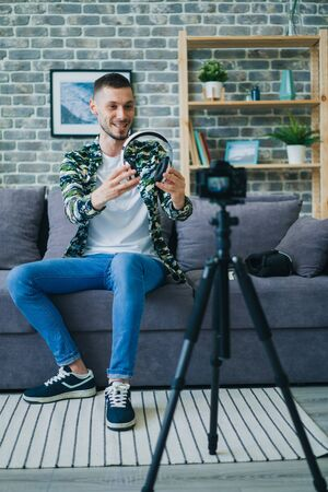 Gadget expert young man is recording video about wireless headphones talking holding device showing for camera at home. People and advertisement concept.