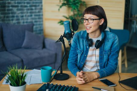 Joyful young woman is talking in professional microphone sitting at table in recording studio working alone. Happiness, emotions and occupation concept.