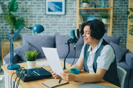 Boy in headphones young blogger is reading in microphone recording podcast in apartment enjoying activity smiling. Happy creative people and blogging concept.