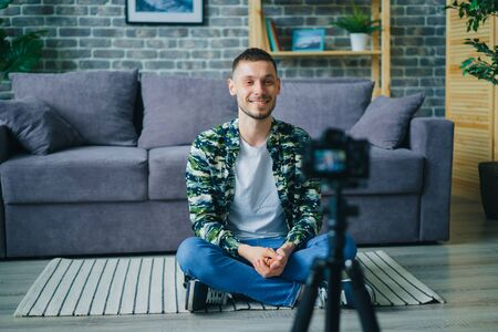 Cheerful young man successful vlogger is recording video for online blog talking looking at professional camera on tripod. Youth and Internet concept. Zdjęcie Seryjne