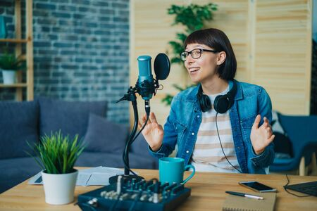 Emotional young woman is speaking gesturing recording audio in microphone at home using modern equipment. People, youth lifestyle and technology concept. 免版税图像