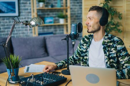 Joyful guy is talking in microphone wearing headphones using laptop in studio sitting at desk alone creating podcast. Modern mass media and equipment concept. 免版税图像