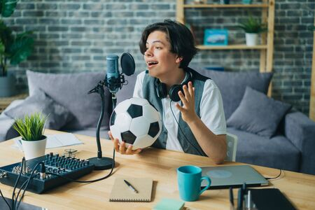 Joyful kid recording audio about football holding ball talking in microphone at home sitting at table alone. Youth lifestyle, sports fans and technology concept.