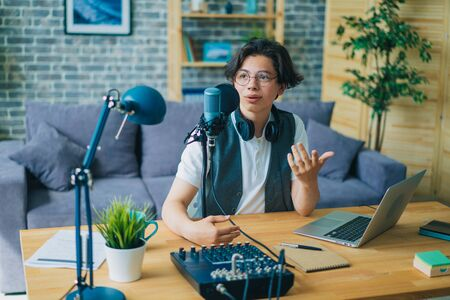 Creative smiling teenage blogger recording podcast audio in microphone sitting at table at home talking in microphone. Youth and blogging concept.