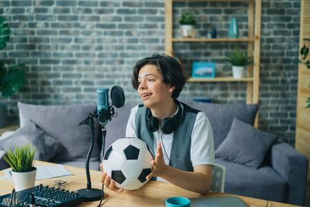 Happy teenager sports fan is talking in microphone in recording studio holding football creating content for internet blog. Youth and modern lifestyle concept.