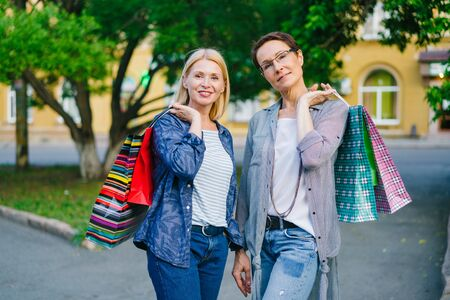Portrait of pretty mature women friends with bright shopping bags looking at camera together outdoors in city street on summer day smiling looking at camera.