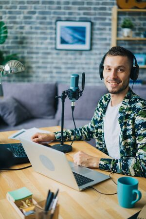 Portrait of guy blogger in headphones in recording studio sitting near microphone smiling looking at camera. Blogging, modern technology and people concept. 免版税图像