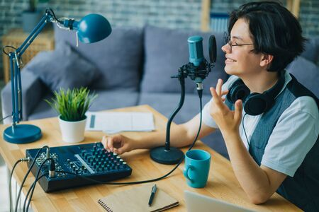 Stylish smart teenager recording audio for internet blog speaking in microphone using sound mixer indoors. Blogging and contemporary equipment concept. 免版税图像