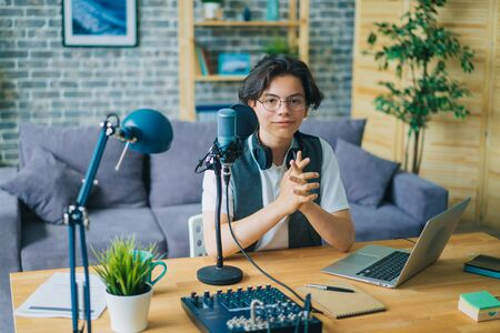 Teenager using microphone and laptop recording podcast in apartment sitting at table looking at camera. Audio blogging, people and communication concept.