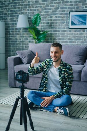 Joyful guy professional vlogger recording content for internet video blog using camera showing thumbs-up smiling. Blogging and modern people concept.