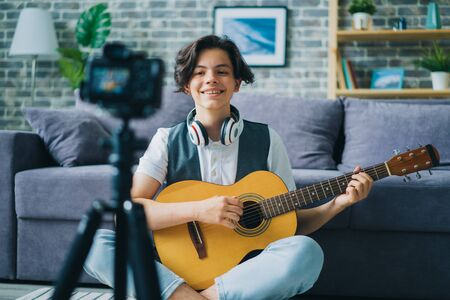 Portrait of teenage blogger recording video at home holding guitar smling using professional camera on tripod. Modern technology and vlogging concept.