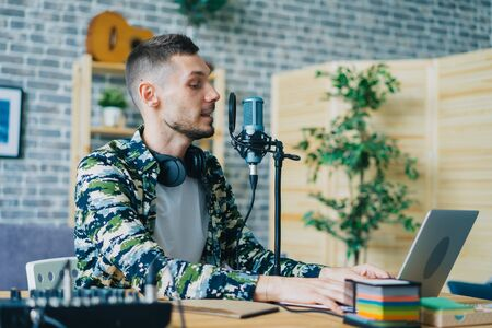 Handsome guy is using professional microphone and laptop talking recording podcart in apartment enjoying occupation. Bloggers and modern technology concept.