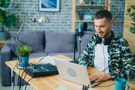 Young man is using laptop in sound recording studio smiling looking at screen. Modern technology, contemporary profession and successful youth concept. 免版税图像