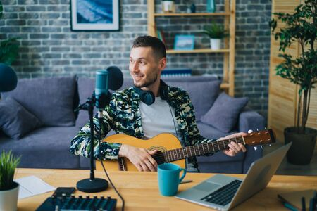 Handsome guy is playing the guitar recording audio podcast in studio using microphone and laptop sitting at table indoors alone. People and music concept.