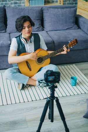 High angle view of happy child vlogger playing guitar recording video for internet vlog using professional camera on tripod. Youth and blogging concept.
