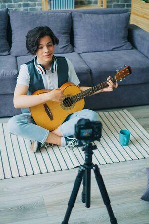 Vue en grand angle d'un vlogger enfant heureux jouant de la guitare pour enregistrer une vidéo pour un vlog Internet à l'aide d'une caméra professionnelle sur un trépied. Concept de jeunesse et de blogs. Banque d'images