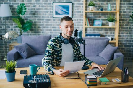 Joyful bearded guy is reading in microphone holding paper making podcast in studio enjoying occupation. Happy people, communication and blogging concept. 免版税图像