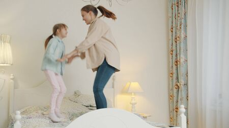 Mother and daughter are jumping in bed having fun holding hands enjoying free time indoors. Family activities, people and modern lifestyle concept. Zdjęcie Seryjne