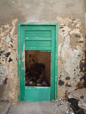 flaking: Old flaking busted green door in white wall Fuerteventura Canary islands Spain