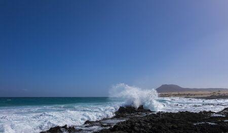 mare agitato: Mare agitato e un'onda schiantarsi contro una roccia con la montagna sulla spiaggia di Corralejo, Isole Canarie, Spagna