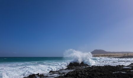 rough sea: Rough sea and a wave crashing against a rock with Mountain on Corralejo beach, Canary islands, Spain Stockfoto