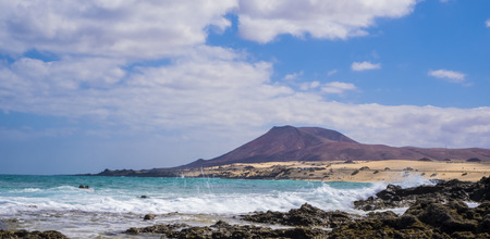 rough sea: Rough sea and blue sky with Mountain backdrop on Corralejo beach Canary islands Spain