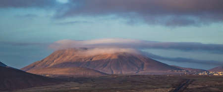 hazy: Bright hazy sun and shadows on a mountain with low cloud in Corralejo, Fuerteventura, Canary-islands, Spain Stock Photo