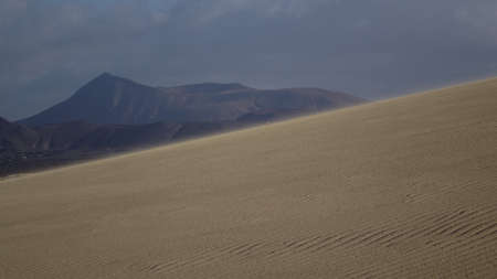 corralejo: Sand pattern with slope and mountain backdrop , Park Natural, Corralejo, Fuerteventura, Canary islands Stock Photo