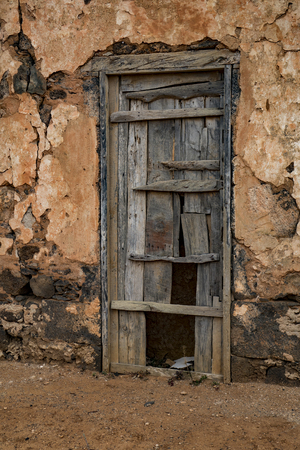 Unusual and interesting picture of a ruin with wooden door with texture and colour in Fuerteventura Las Palmas in the Canary-Islands Spain