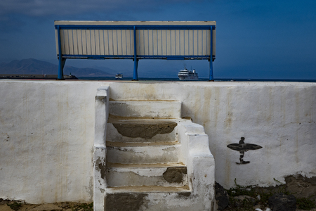 Unusual and interesting picture of a white wall with steps and a seat with texture and colour in Fuerteventura Las Palmas in the Canary-Islands Spain