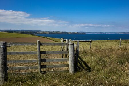 Beautiful rural landscape in Cornwall in bright sunshine on the coast with a gate under a blue sky