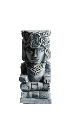 A stone look Mayan god sitting in a traditional cross legged pose. His headdress features a sun and moon. The statue has the characteristics of one that has been carved.
