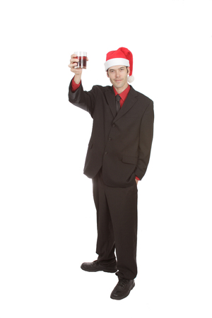 A businessman wearing a dark suit, red top and Santa hat. He holds a glass in his hand and looks ready to make a toast. Isolated on white.