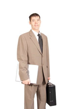 3 4 length: A professionally dressed white collar worker is standing holding a laptop and a briefcase  Three-quarter length and isolated on white