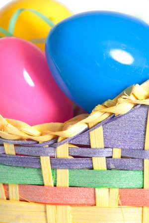 A tightly cropped image of plastic Easter eggs in a basket. Stock Photo