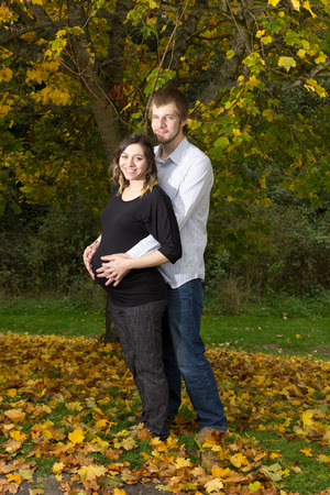 An attractive young couple stand under an Autumn tree with both of them holding her pregnant belly  photo