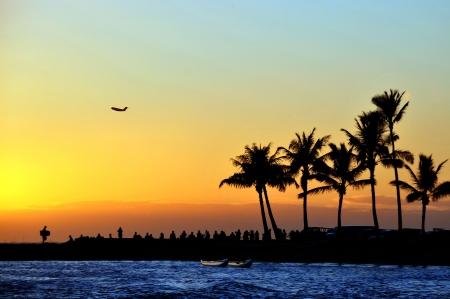 人々 は、ビーチで夕日を見る